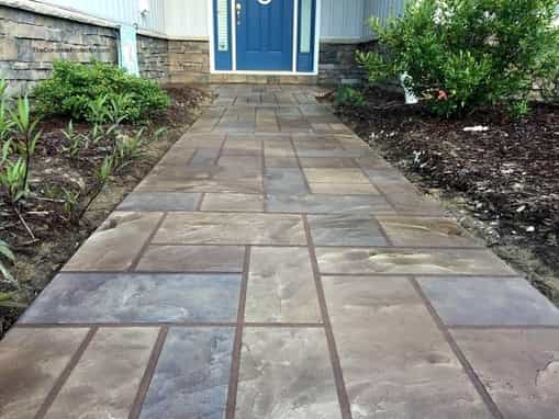 Stamped and stained concrete sidewalk.  Concrete is stamped to look like large stone blocks, and stained in browns and greys.