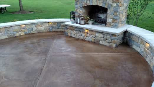 Resurfaced concrete patio.  Integral colored concrete in a dark brown.  Outdoor fireplace in the background.