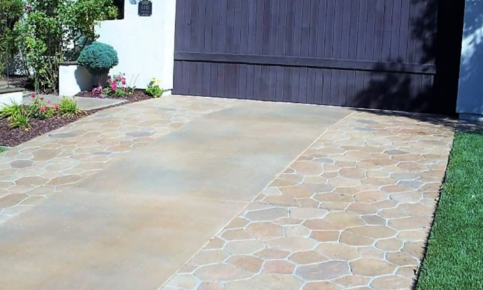 Stamped and colored concrete driveway with grey garage door.